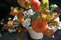 orange, yellow and white fall centerpiece of dahlias, roses, berries and leaves | floral design: Amy Merrick