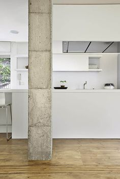 Interior of the Bonanova Apartment renovation in Barcelona by Maria Castello. Minimal interior design with focus on beautiful textured concrete column. This is what minimalism is about.