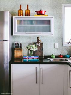 Cozinha clean com revestimento de pastilhas de vidro e marcenaria em branco.