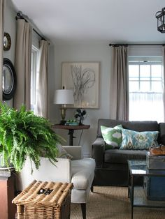 A white arm chair, grey sofa, patterned throw pillows and pedestal side table create an eclectic look