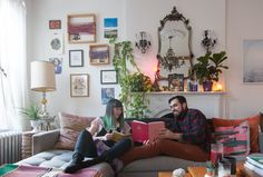 Courtney and Jeff relax in their living room. This warm and welcoming apartment teeters between adult and whimsical, with a style as unique as the inhabitants.