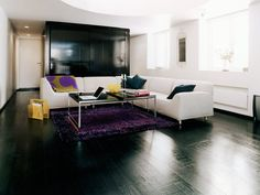 Staining hardwood floors black can anchor a large space while maintaining its elegance. When stained properly, these floors won't show scratches or scuffs.
