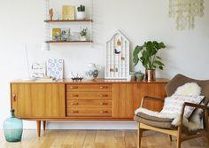 Ein echter Hingucker ist dieses Sideboard im Stil der 60er-Jahre. Kombiniert mit einem Retro-Sessel und passenden Dekoobjekten verleiht es dem Zimmer einen charmanten 60er-Look. Eine moderne Tischleuchte und ausgewählte Accessoires sorgen für eine zeitgemäße Note.