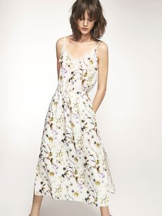 Koronkowa sukienka w kwiatowy deseń uszyta ze 100% jedwabiu morwowego, o rozkloszowanym kroju, z dekoltem w szpic z koronkową aplikacją, elastyczną talią, dwiema bocznymi kieszeniami, na cienkich ramiączkach, z rozcięciami po bokach u dołu, na podszewce. Długość sukienki w rozmiarze 38 wynosi 106,2 cm.