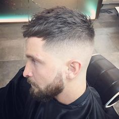 how to style a undercut, man with serious expression, with beard and mustache, hair trimmed very short on the side but kept longer and wavy on top, wearing black hairdresser's robe