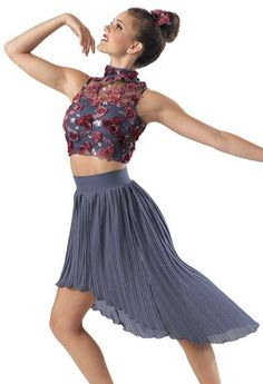 Two-piece costume. The turtleneck top is textured eggplant rosette and embroidered sequin mesh overlaying a slate blue spandex bra top with a back zipper. The pleated georgette skirt is high-waisted and has a high-low hemline, soft spandex waistband and attached trunks. Includes a rosette hair appliqué.