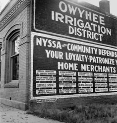 """(Lange) Lange's original caption: """"October 14, 1939. Nyssa, Malheur County, Oregon. Sign on old bank building which now houses the office of the Bureau of Reclamation."""""""