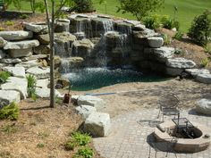 Backyard waterfall, beach & patio with fire pit, this would be awesome, but It would take up my whole back yard!