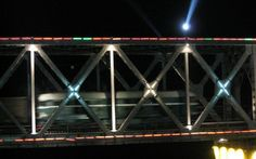 Train going into North Korea by night at Dandong bridge. Photo by Victor Robert Lee.