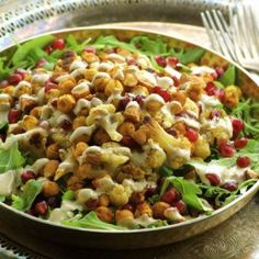 Roasted Cauliflower and Spiced Chickpea Salad : The warm cauliflower and chickpeas top a fresh arugula salad with pomegranates and almonds
