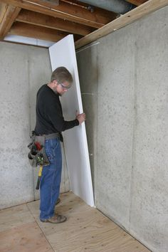 Photo of Andy Engel installing EPS insulation on the interior of a basement wall