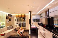 Apartamento pequeno, living, sala de jantar, cozinha, lavanderia, quarto, banheiro e sacada. Decoração com bandeira, painel preto, painel de vidro, tapete escuro e persiana de madeira. Projeto de Camila Klein.jpg