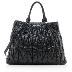 A trendy Miu Miu tote in quilted black leather with silver-tone hardware. Details include two rolled handles, a magnetic snap closure, and fully lined interior with one zippered pocket. Carry this style on the forearm or over the shoulder with a detachable strap.