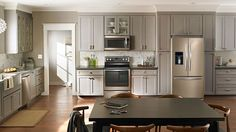 The Whirlpool Sunset Bronze with light dove grey cabinets in a well lit kitchen.