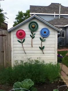 Hubcap flowers, hose/pipe stems - perfect for a chicken coop, goat shed, garage side...