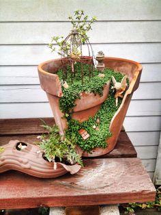 Fairy garden in a broken pot. Great way to recycle.