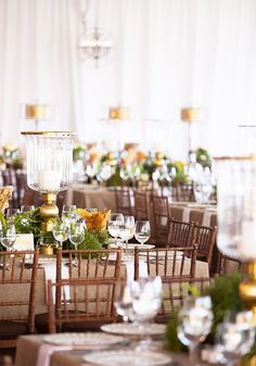 Dinner party with wood chairs, hanging lanterns, hurricane candles, white and brown tablecloth, and plants
