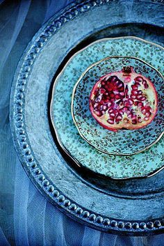 Rustic blue plate and charger serving up a juicy pomegranate.