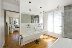 """""""The old living room and balcony on the sixth floor were transformed into the master bedroom with an en-suite open bathroom,"""" Hammer said. Flos lighting illuminates the space above the vanity."""