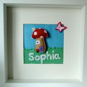 Felt Box Frame - Mounted & personalised. Hand cut felt toadstool which is slightly padded, with a flower lined path and a 3D butterfly in a 10 inch squared box frame, mounted so that the picture is 4.5 inches square. Each flower, butterfly, toadstool is hand cut and hand stitched by me and is very labour intensive. This is just an example of the pictures I can do. Prices for these start at £20 depending on the size of the picture and the level of detail required. This one is £26.