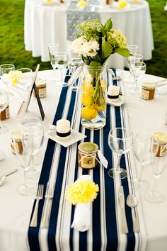 Navy striped runner, candle on a plate, and simple vase with white flowers (hydrangeas or tulips).