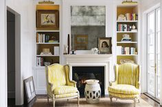 Two armchairs upholstered in yellow flanking a garden stool in front of a fireplace mantel in a sitting room with French doors. Interior design by Susan Greenleaf. | Lonny.com