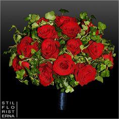 Klassisk elegant brudbukett i hållare med röda rosor och murgröna.