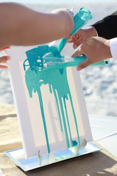 The bride and groom poured and mixed two shades of paint onto a canvas as a unique unity ceremony