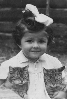 Girl with a bow in her hair, and two tabby cats.