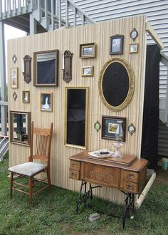 Photo booth with wall of frames cut out and black curtain behind.
