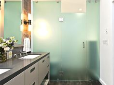 An opaque glass-enclosed shower is adjacent to a long taupe vanity that has two built-in sinks and large mirror. Soft lighting in the room is provided by a sconces near the vanity and recessed lighting in the shower to create a tranquil, relaxing space. Contemporary Bathrooms, Modern Bathroom, Master Bathroom, Bathroom Inspiration, Bathroom Ideas, Design Bathroom, Bathroom Interior, Transitional Bathroom, Glass Shower Doors
