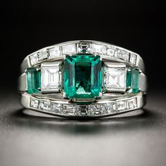 A dynamic and distinctive (as in one-of-a-kind) original Art Deco dazzler featuring a vibrant crystalline green Colombian emerald weighing 1.20 carats. The exceptional and stunning gemstone is accompanied east and west by a pair of bright white and shining, almost square, baguette diamonds followed by smaller emeralds, and guarded north and south by gently curved rows of small square-cut diamonds to resemble a three piece set. This singular and stunning vintage jewel was custom designed and…