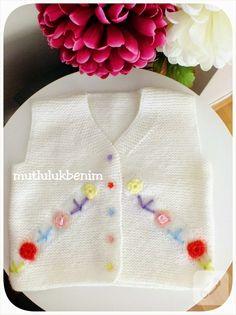 renkli örgü çiçekler ve düğmelerle süslenmiş beyaz bebek yeleği çok tatlı duruyor. en güzel bebek örgüleri, tığ işi ve örgü modelleri ile anlatımlı videolar 10marifet.org'da
