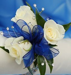 Women in bridal party corsages. Only with silver roses and navy blue ribbon.