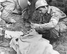 An American medical officer, who landed with the 82nd Airborne Division, hands a lighted cigarette to a member of his organization who had a rather rough landing, at Utah Beach, St. Mere Eglise, France, June 7, 1944. (Photo by PhotoQuest/Getty Images)