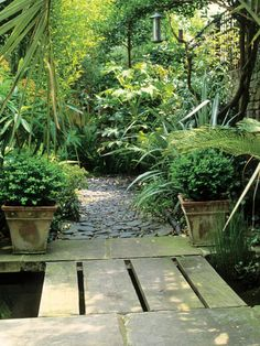 A stone bridge and walkway cuts through a garden planted with lush trees and ferns. Decorative pots flanking the walkway hold stylish topiary plants.