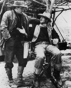 "James Arness and John Wayne talk things over during a break in the making of ""Hondo"". ('53 WB)."