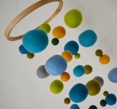 Designed entirely with eco friendly materials, this mobile features vibrant wool balls that float, twist, and twirl with every whirl of air. Strands of solid hand needle felted wool balls hang from a wooden ring. Simply loop the string at desired length and hang from ceiling hook!  Felted ball mobile for baby