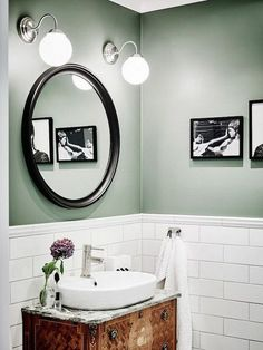 Bathroom with green walls, white subway tiles and antique vanity.