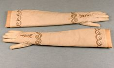 A pair of ladies long white cotton fabric embroidered gloves, circa 1790 - 1810, the lawn fabric cut on the bias to give stretch, the plain weave raw edges turned inside then delicately overstitched on the outside; with gold and sequinned scrollwork and pale pink floss silk detailing, 58 cm long.