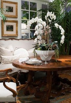 White walls, sofa flowers, etc. with nice wood table, prints.
