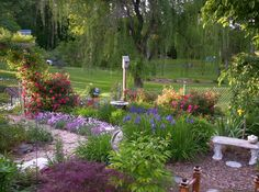 Flowers image: Memory Garden Spring: Memory garden in the spring with knock out roses, 'happy returns' daylily, coreopsis, salvia, purple coneflower, dianthus, speedwell, and Japanese iris. From Farmers Almanac