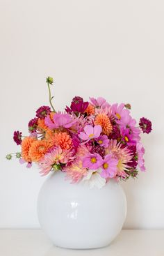 Domed English grown Dahlias in gold fish bowl with scabious detail in orange and pink shades Corporate arrangement by Okishima & Simmonds Limited London www.okishimasimmonds.com