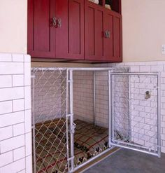 possible idea for garage kennel.Stylish Dog Kennel: A built-in, chain-link kennel outfitted with two dog beds provides the perfect indoor shelter for your furry friends. Cabinets and cubbies store pet food and other supplies. Vintage Baby Rooms, Designer Dog Beds, Dog Area, Dog Rooms, Ideias Diy, Up House, Food House, Garage House, Dog Houses