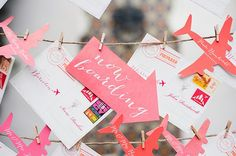 Get inventive with your travel theme by integrating classic travel icons into your decor, such as airplanes, trains, boats suitcases or even tickets. String paper airplanes together to create a lovely photo backdrop or use cutout planes to seat your guests. | Jessica Kettle via Amorology Weddings