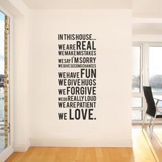 "Black family rules wall sticker placed on an off-white wall in a modern family room. The vinyl rules includes reminders that ""we are"" real, loving, fun, etc."