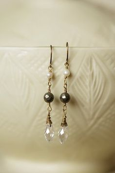 Unique dangle pearl and crystal earrings for women are featured on antique brass