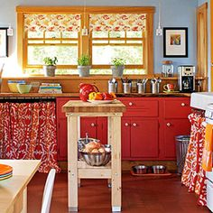DIY kitchen style. A simple movable island stands in for a more expensive built-in cabinetry piece. Fabric skirts hide undercounter storage. Open shelving stores often-used dishware, and paint brightens inexpensive cabinets. Folded tea towels mounted on tension rods make an easy, budget window treatment. More kitchens: http://www.midwestliving.com/homes/room-decorating/kitchen-styles/page/19/0