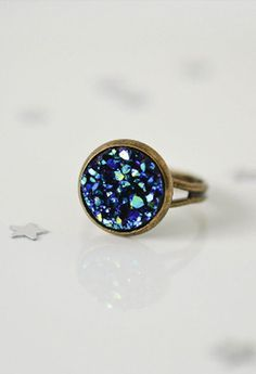 This beautiful druzy ring was made using a blue faux druzy resin cabochon that has a shimmer just like a real druzy. It is attached to an adjustable bronze ring. All of our rings come in a cotton line