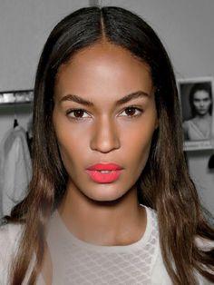 Joan Smalls bright pinky red lipstick  | allure.com